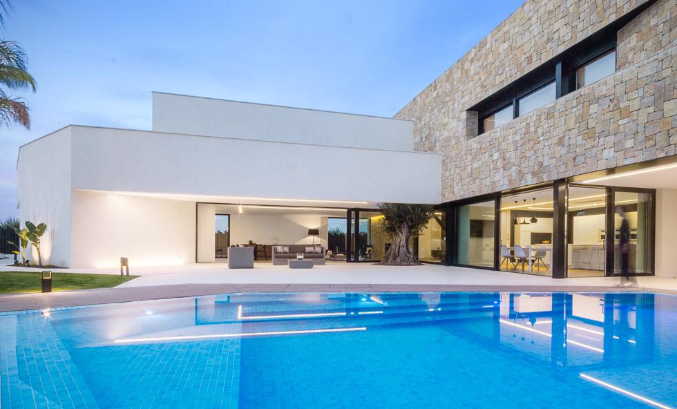 Casa de diseño Cumbres minimalista con muro de piedra y piscina desbordante | Chiralt arquitectos Valencia