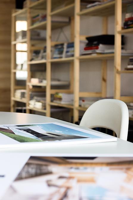 Mesa de reuniones blanca en despacho con libreria de madera al fondo