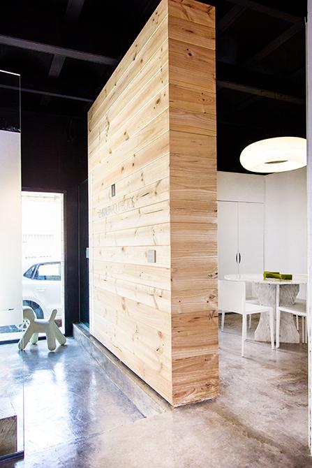 Separador de madera en despacho con mesa de reuniones redonda de marmol