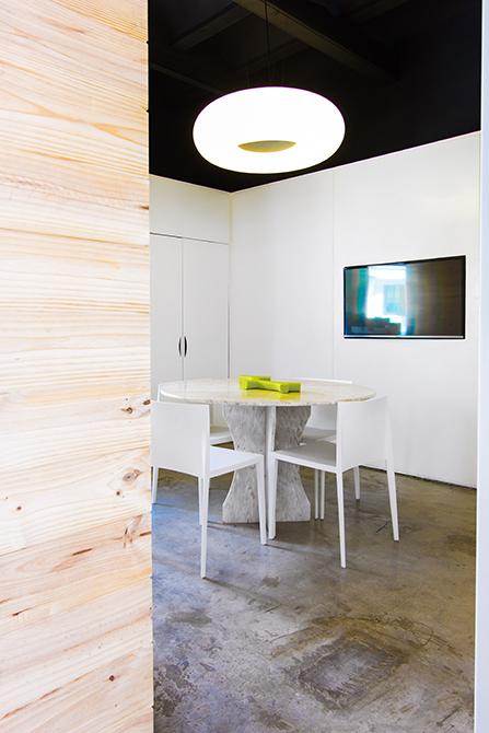 Despacho con mesa de reuniones redonda de marmol y lampara donut