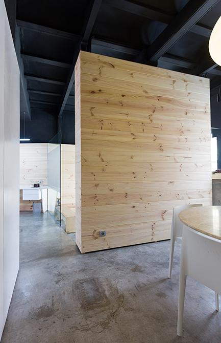Mueble de madera separador en despacho con mesa de reuniones redonda de marmol