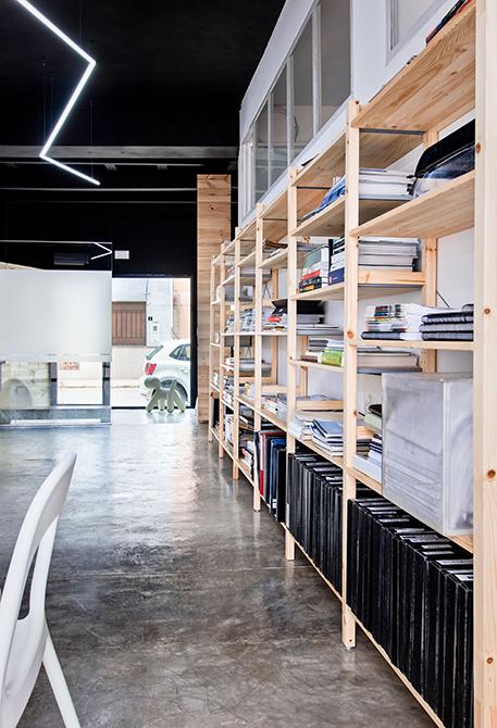Libreria grande de madera en despacho con suelo de hormigon pulido