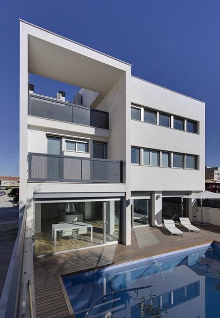Casa moderna con piscina. Patio de madera moderno y blanco. Casa abierta a la terraza