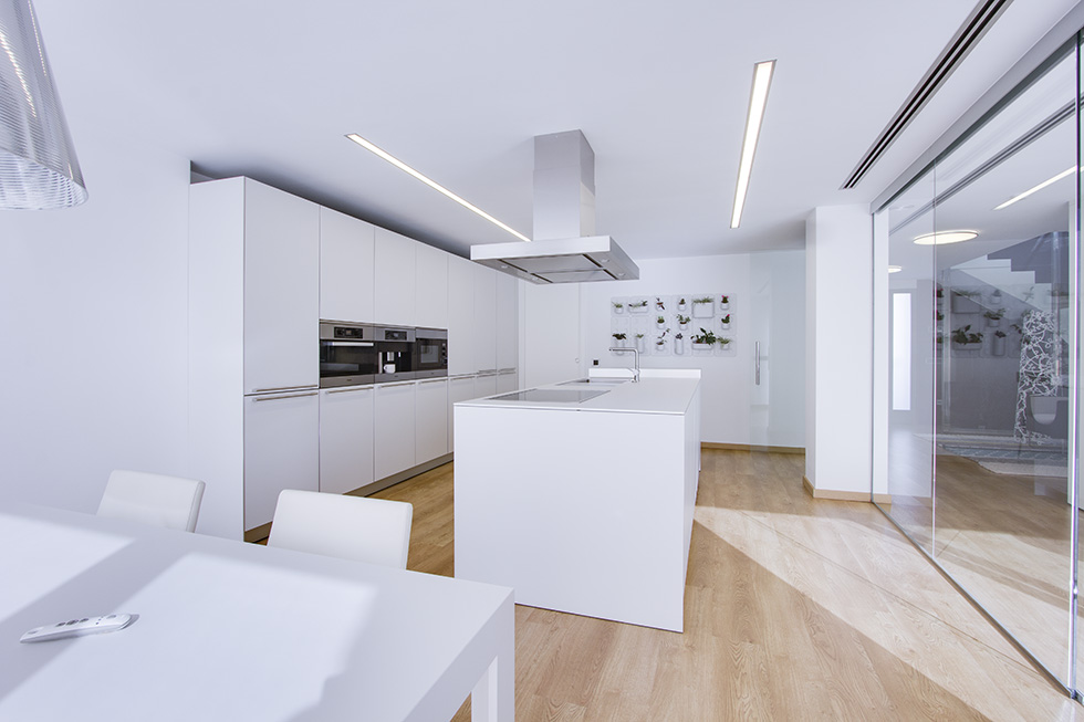Cocina con isla blanca, grande y con campana. Suelo de madera. Cocina minimalista y moderna con cristal. Mesa de cocina blanca