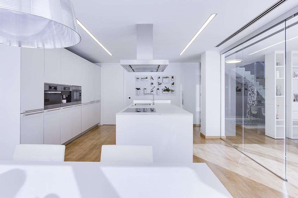 Cocina con isla blanca, grande y con campana. Suelo de madera. Cocina minimalista y moderna con cristal