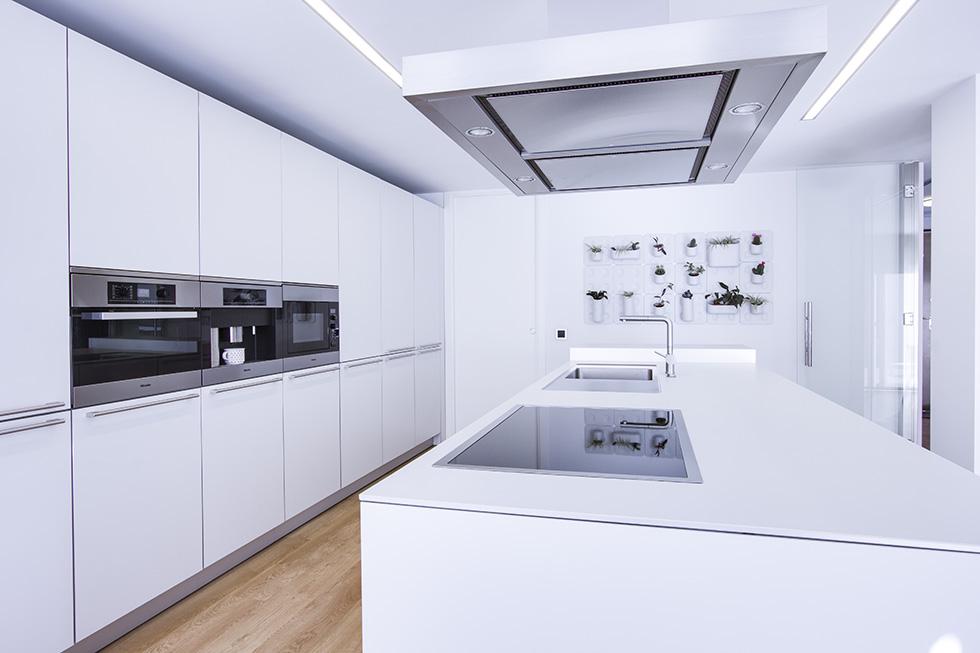 Isa de cocina blanca, grande con encimera y pila blanca. Suelo de madera.