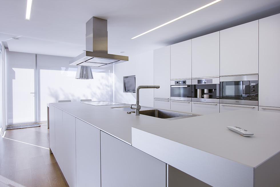 Cocina blanca grande, con isla central con encimera y fregadero. Abierta al jardín con grandes ventanales.