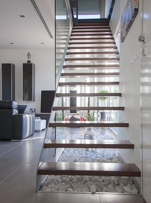 Escalera con peldaños de madera y barandilla de cristal en casa minimalista. Chiralt Arquitectos Valencia.
