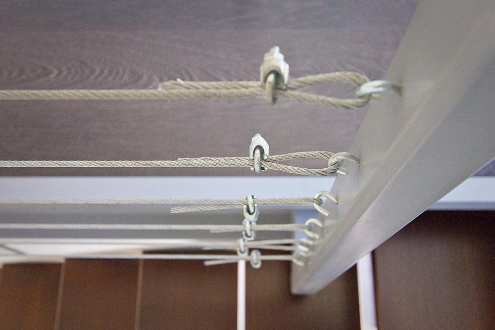 Escalera con peldaños de madera y barandilla de cables de acero en casa minimalista. Chiralt Arquitectos Valencia.