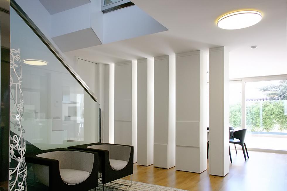 Recibidor con vistas al jardín y el salón y libreria blanca como separador de espacios