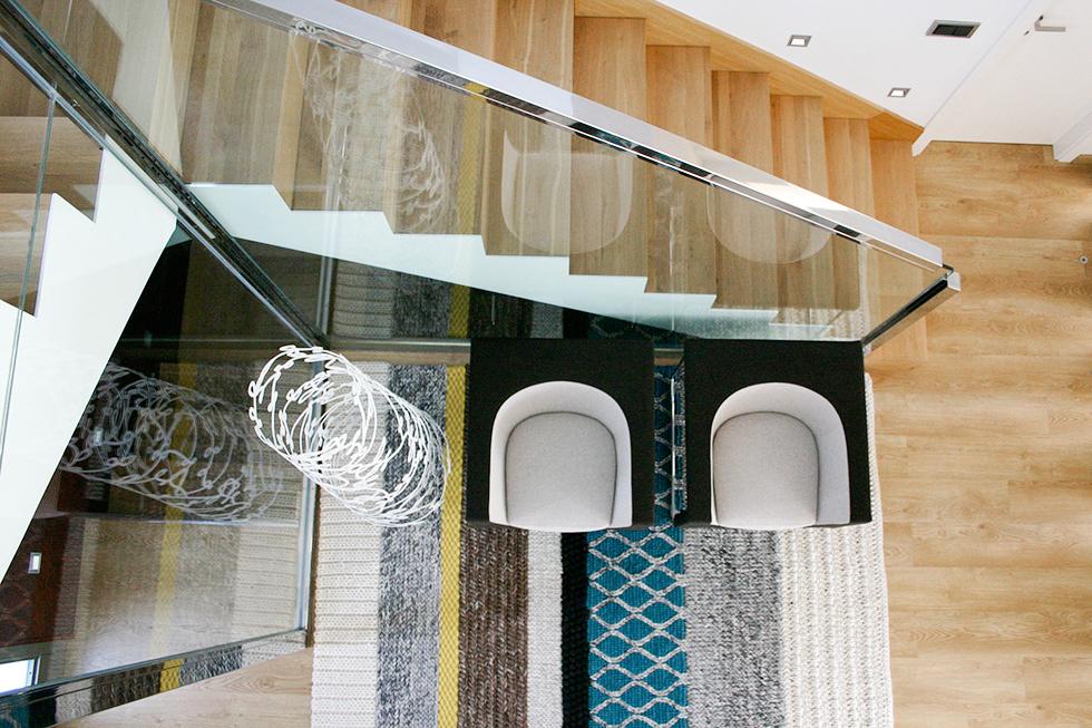 Recibidor moderno con escalera de madera y barandilla de acero y cristal, con sillones Stua y alfombra Gan.