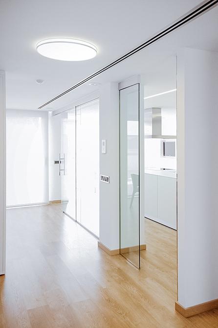 Pasillo con puerta de cristal a la cocina con ventanal y mucha luz