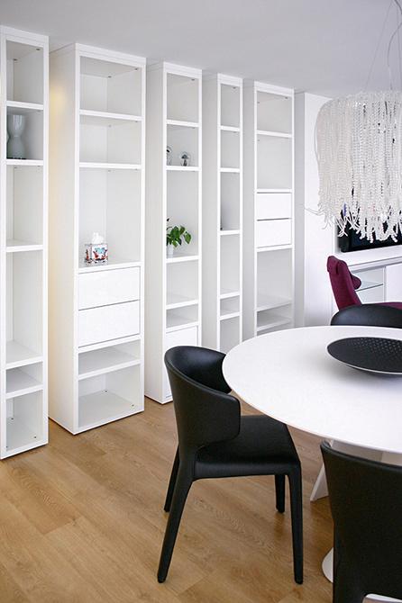Librería blanca y moderna con mesa de comedor blanca y redonda y sillas negras