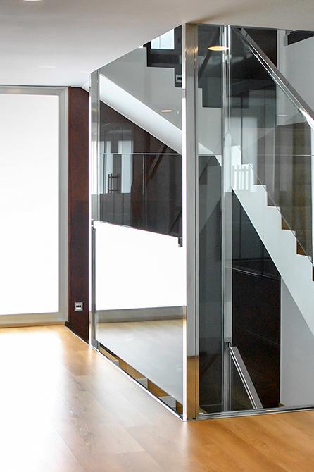 Escalera moderna con barandilla de acero y cristal con ventanal y mucha luz