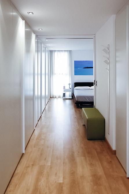 Dormitorio amplio y moderno en madera y blanco con gran ventana