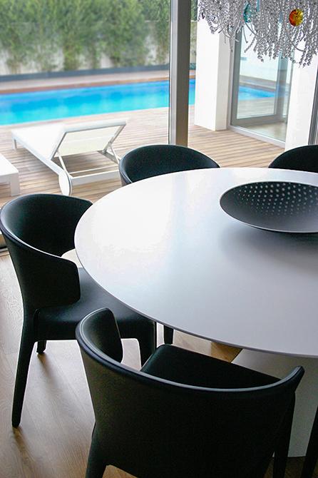 Mesa de comedor moderna con vistas a la terraza y la piscina. Siilas negras y mesa redonda blanca