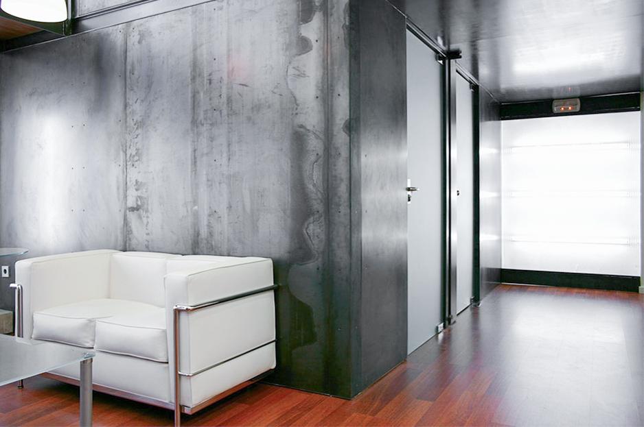 Recibidor moderno de academia de idiomas con sillon blanco y pared de acero
