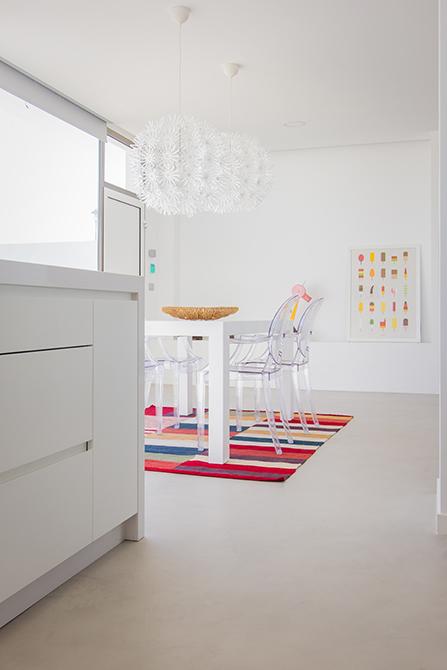 Isla de cocina blanca y mesa de comedor blanca con alfombra multicolor