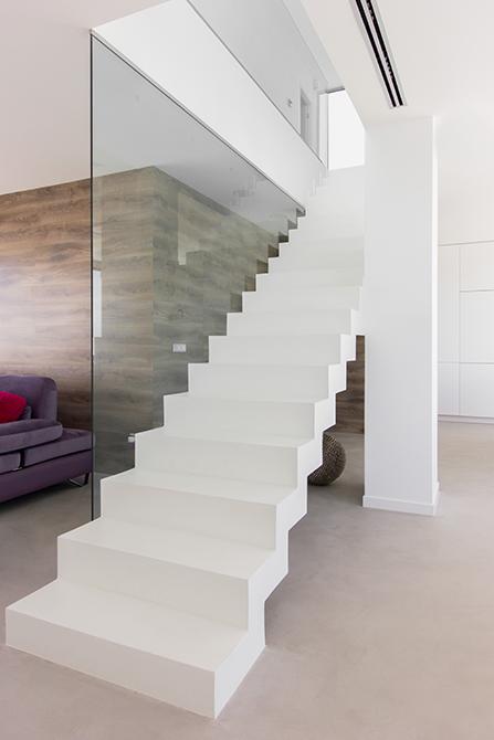 Escalera de microcemento blanco en salon. Suelo de microcemento gris