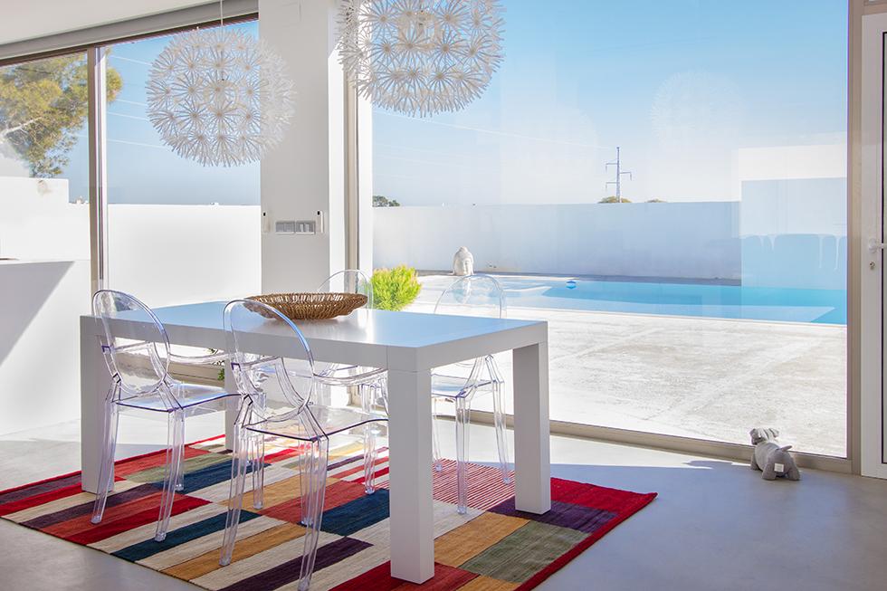 Mesa de comedor blanca y moderna con vistas a la piscina. Alfombra multicolor
