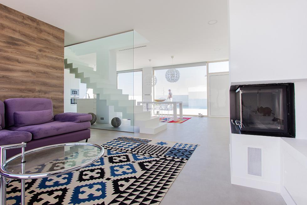 Salón moderno abierto a la cocina blanca. Escalera de microcememto blanco. Cocina con vistas a la piscina