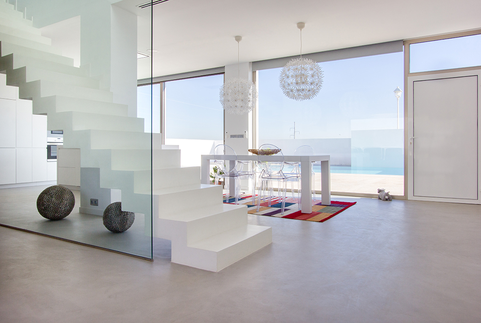 Escalera minimalista de microcemento blanco en cocina de casa mediterránea. Mesa de cocina moderna con vistas a la piscina