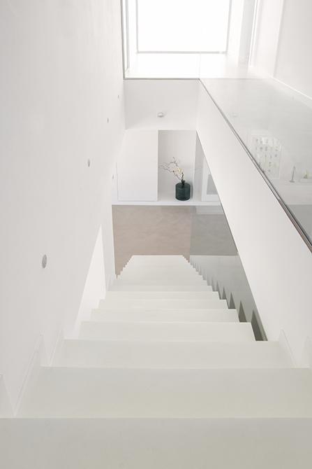 Escalera minimalista de microcemento blanco. Pasillo de microcemento gris