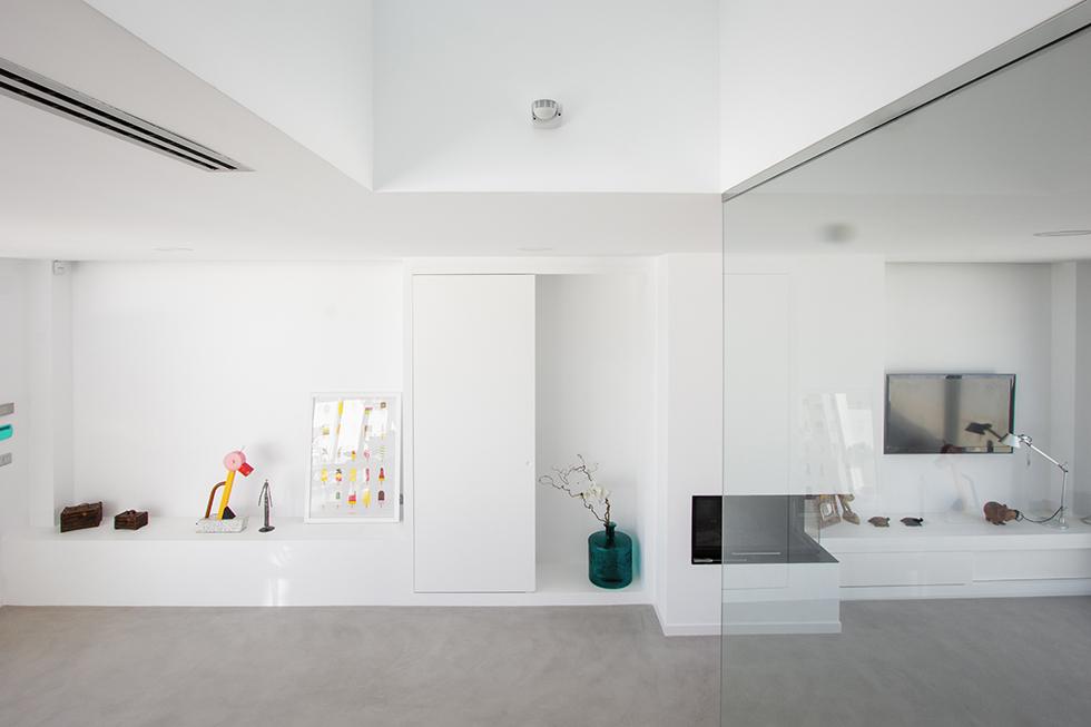 Salón comedor minimalista con suelo de microcemento. Chimenea moderna integrada.