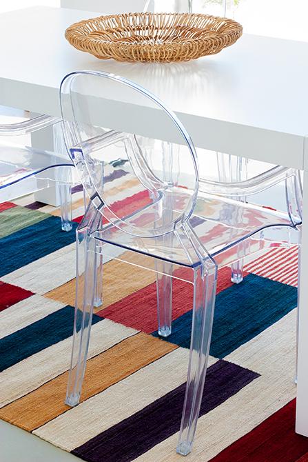 Silla transparente en mesa de cocina con alfombra de colores