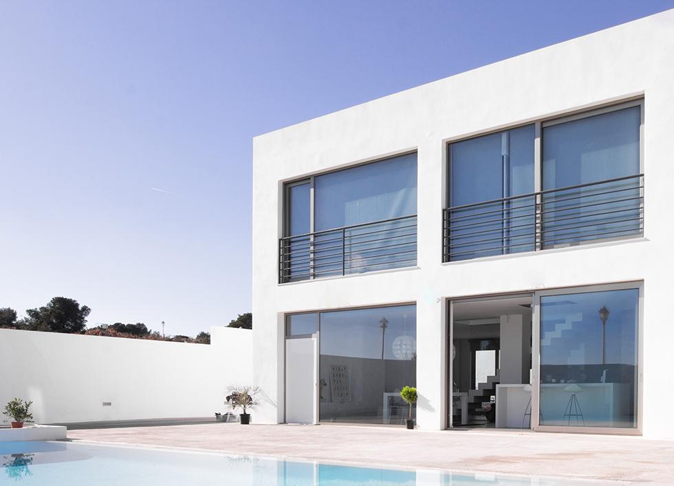 Fachada blanca. Casa moderna con grandes venatanales. Piscina de diseño en la terraza