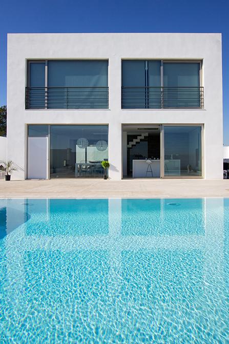 Piscina de microcemento blanco. Fachada blanca de casa moderna y minimalista. Casa abierta al exterior