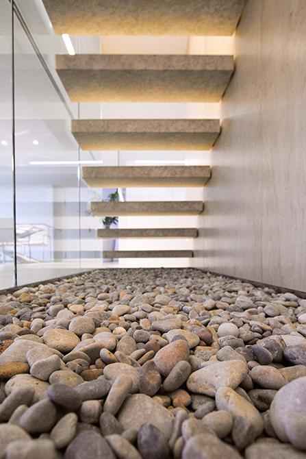 Escalera de peldaños de piedra volados. Barandilla de cristal y piedras en el hueco bajo escalera