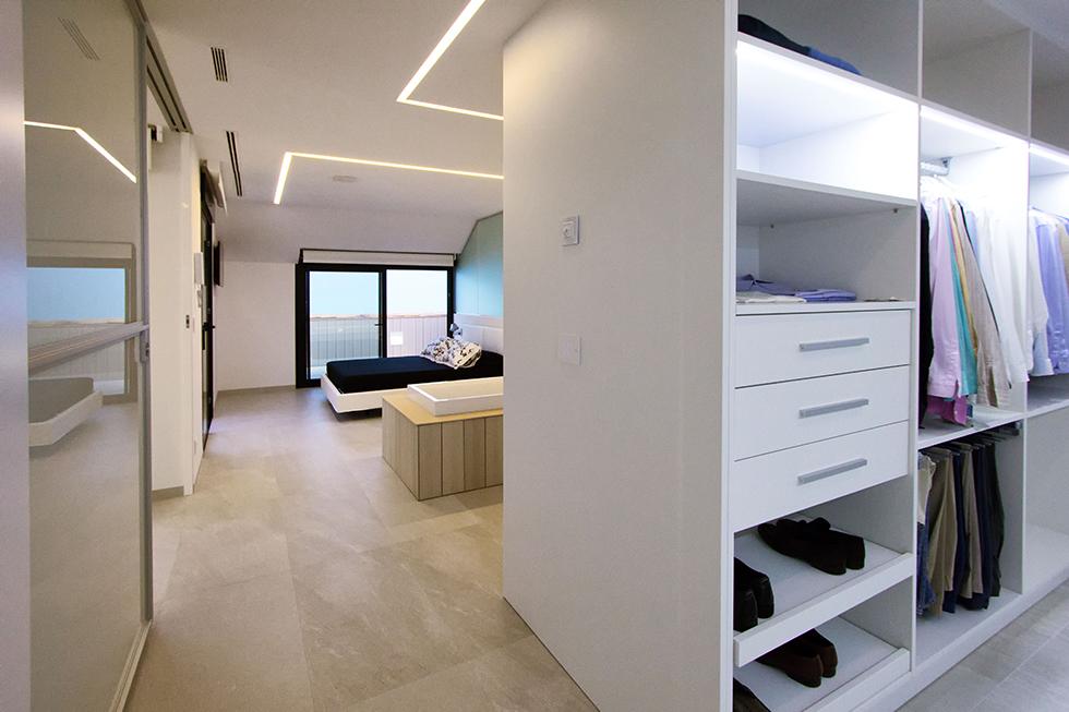 Habitación buhardilla con bañera y vestidor abierta.Terraza con tumbonas blancas. Chiralt Arquitectos Valencia