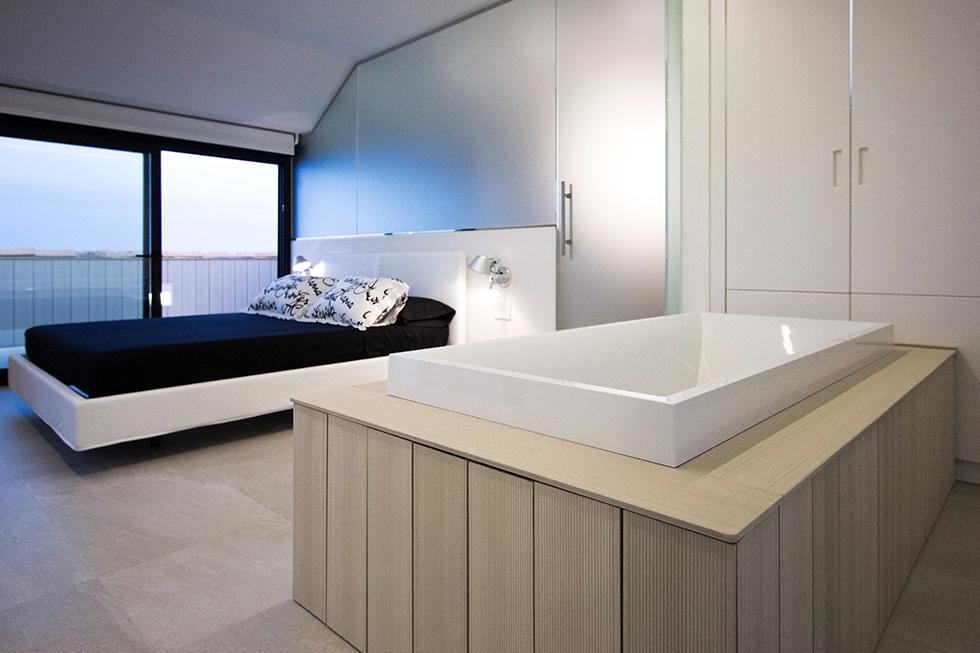 Habitación moderna en buhardilla con bañera exenta y vestidor abierto. Colores blanco y negro Chiralt Arquitectos Valencia