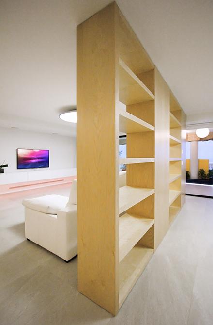 Estantería hasta el techo de madera clara divisoria entre salón y comedor