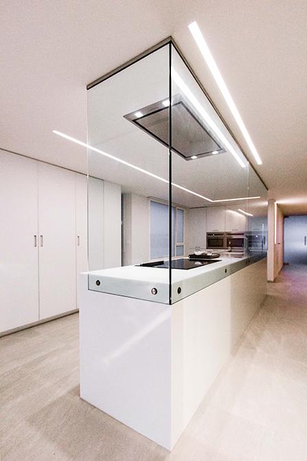 Isla blanca en cocina minimalista abierta al salon, con mampara de cristal