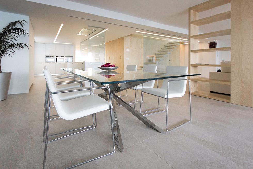 mesa de cristal moderna en comedor cocina.Habitación buhardilla con bañera y vestidor abierta.Terraza con tumbonas blancas. Chiralt Arquitectos Valencia