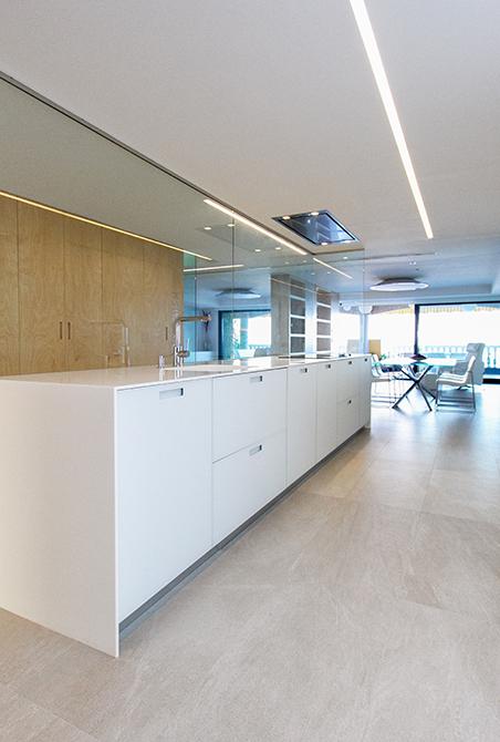 Isla de cocina blanca con pared de cristal. cocina abierta al salon Chiralt Arquitectos Valencia
