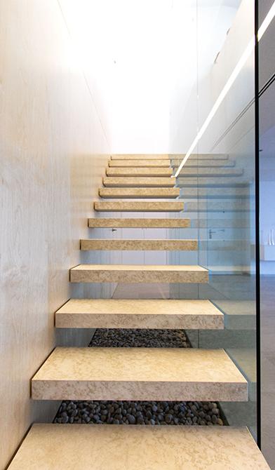Escalera de peldaños volada. escalera de piedra con barandilla de cristal