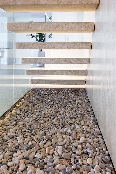 Escalera de peldaños volada. escalera de piedracon barandilla de cristal