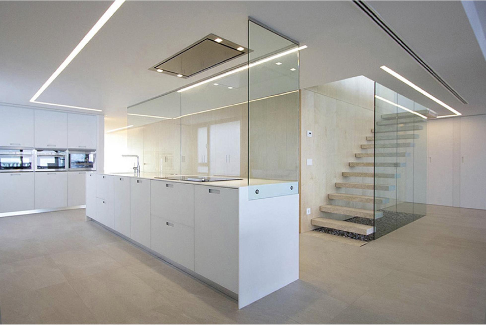 Isla de cocina blanca y abierta al salon. Escalera de peldaños de piedra volados con barandilla de cristal