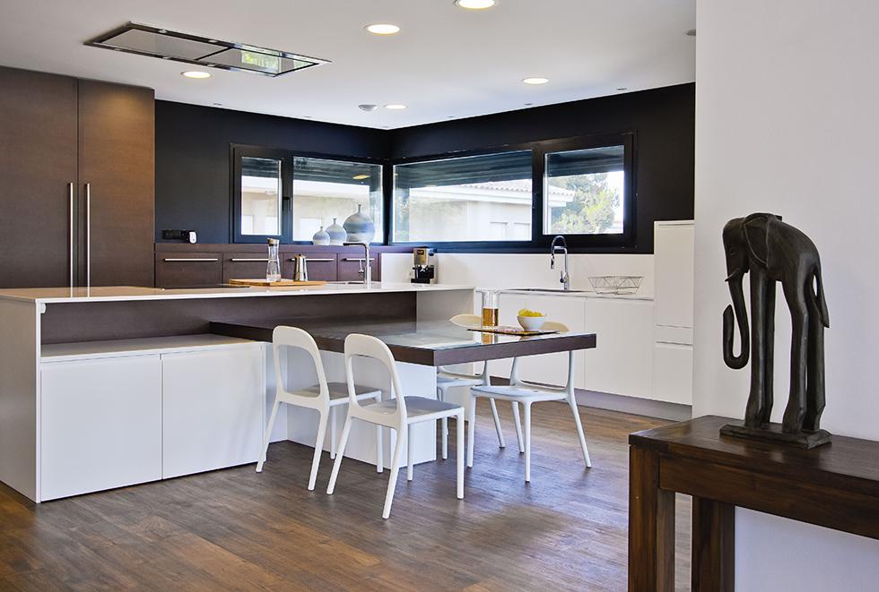 Cocina moderna en blanco y negro con suelo porcelánico efecto madera en casa passive