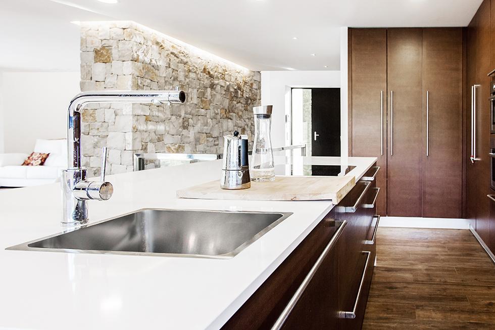 Cocina moderna y abierta al salón con muro de piedra, en madera y blanco, con suelo porcelánico efecto madera en casa pasiva