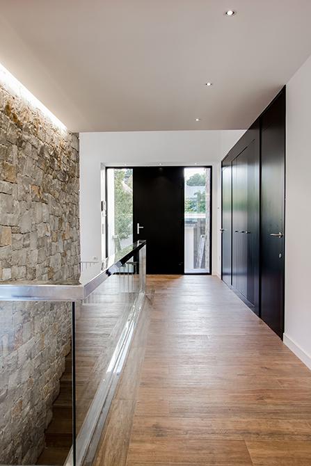 Recibidor con muro de piedra, con suelo porcelánico efecto madera en casa pasiva |
