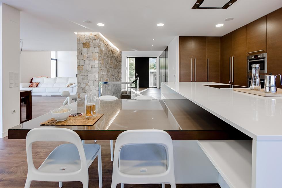 Cocina moderna y abierta al salón, en madera y blanco, con suelo porcelánico efecto madera en casa pasiva