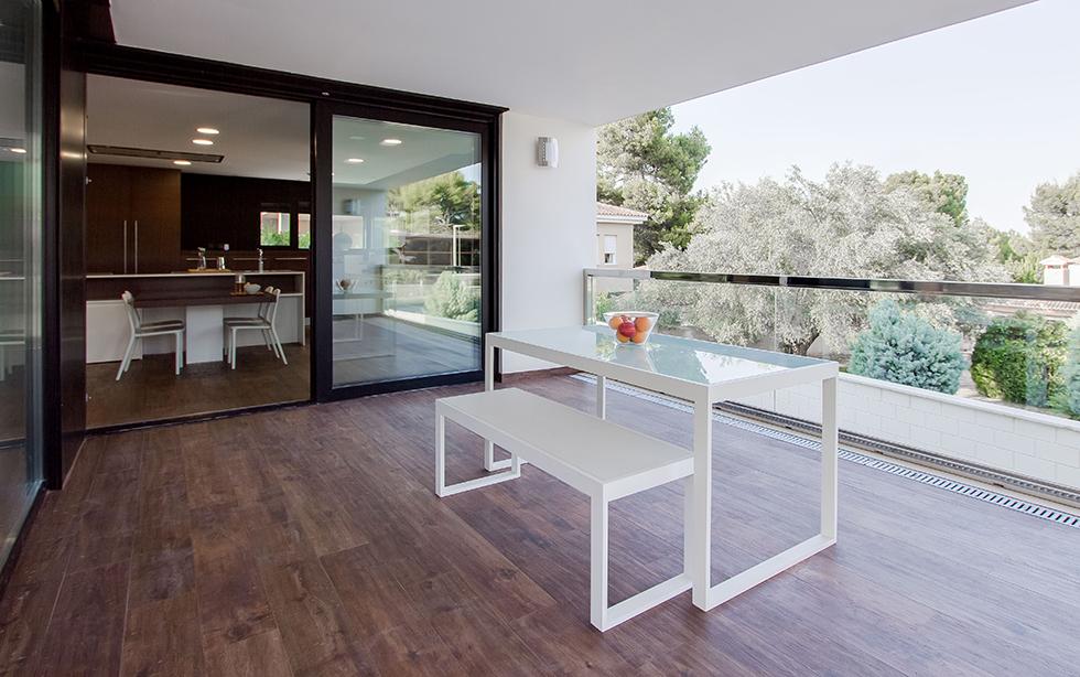 terraza cubierta en casa moderna con mesa de exterior blanca y banco