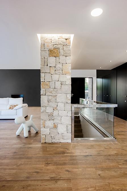 Salón y entrada con muro de piedra, con suelo porcelánico efecto madera en casa pasiva | Chiralt Arquitectos Valencia