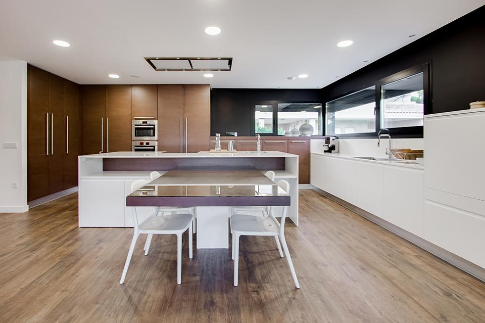 Cocina moderna y grande con isla central y mesa para comer