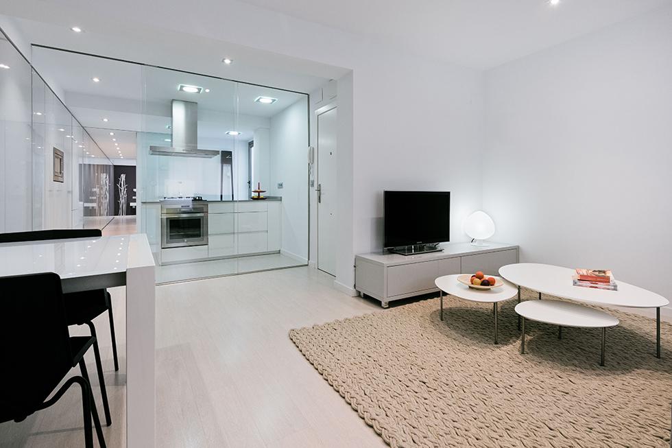 Comedor y cocina modernos y abiertos en apartamento pequeño en blanco y gris