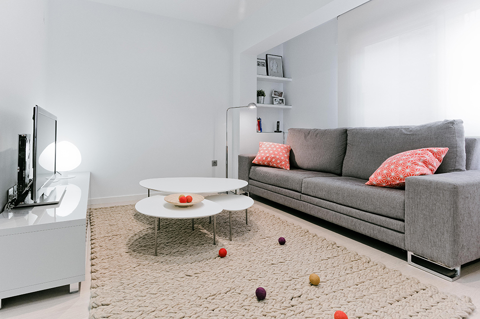 Pequeño salon apartamento en blanco y gris.